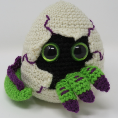 Hatching Dragon Egg Amigurumi by Kati Brown from Hooked by Kati. A little dragon is seen peeking through the egg shell.