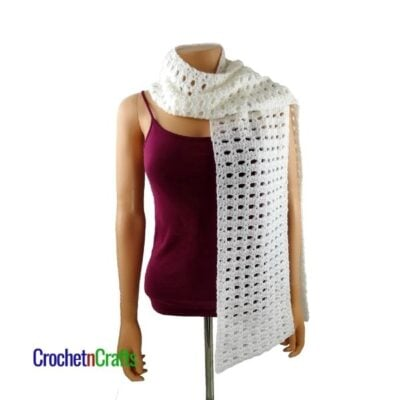Half Double and V-Stitch Easy Crochet Scarf by CrochetnCrafts. The scarf is draped around the neck and over the shoulder.