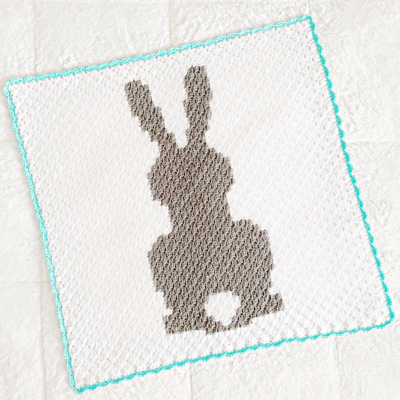 Baby Bunny Blanket by Melissa Hassler from Lovable Loops. It's a beautiful C2C blanket featuring a gray bunny with a white bushy tail.