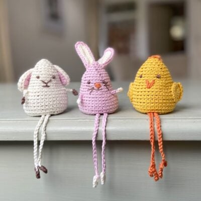 Amigurumi Crochet Animals: Easter Chick, Lamb, & Bunny. The amigurumi chick, lamb and bunny are seated on the edge of a shelf with the legs dangling over the edge.