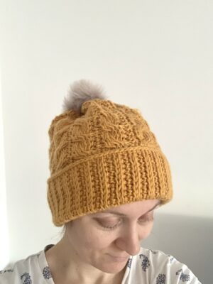 Winding Cables Hat by Miroslava Mihalkova from Exquisite Crochet UK. This Tunisian cabled hat features a pom pom and a wide brim that can be folded over for a super cozy winter hat.