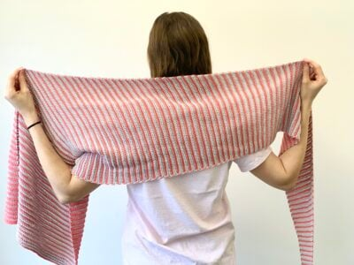 Seeing Stripes Shawl by Miroslava Mihalkova from Exquisite Crochet UK. The assymetrical shawl is held up behind the back and shown in two colors.