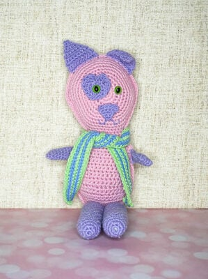 Love Critter by Marie Segares/Underground Crafter. The amigurumi pattern is shown in pink and purple with a purple spot around the eye and a green and blue scarf tied around the neck.
