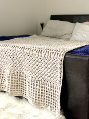 Marks In The Snow Throw by Miroslava Mihalkova from Exquisite Crochet UK. The white throw is draped over the foot of a bed.