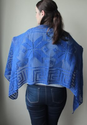 Electric Blue Filet Crochet Shawl by Veronika Cromwell from Blue Star Crochet. The shawl features a beautiful flowery and maze design.
