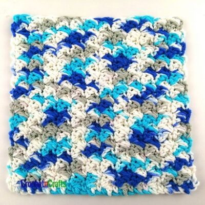 Seed Stitch Crochet Dishcloth Pattern by CrochetnCrafts. It is shown in a variegated yarn with blues, a white and gray colors.
