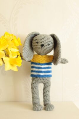 Theo Crochet Amigurumi Pattern by Veronika Cromwell from Blue Star Crochet. The amigurumi has long ears and a striped sweater.