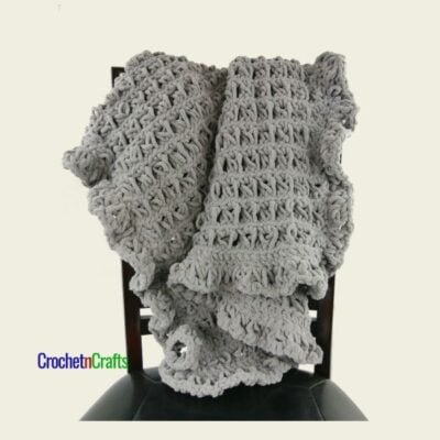 Broomstick Lace Crochet Baby Blanket by CrochetnCrafts. The gray blanket is draped over the back of a chair.