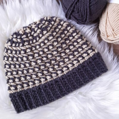 Trinity Stitch Chunky Hat by Sarah Ruane from Ned & Mimi. The hat is shown in two colors.
